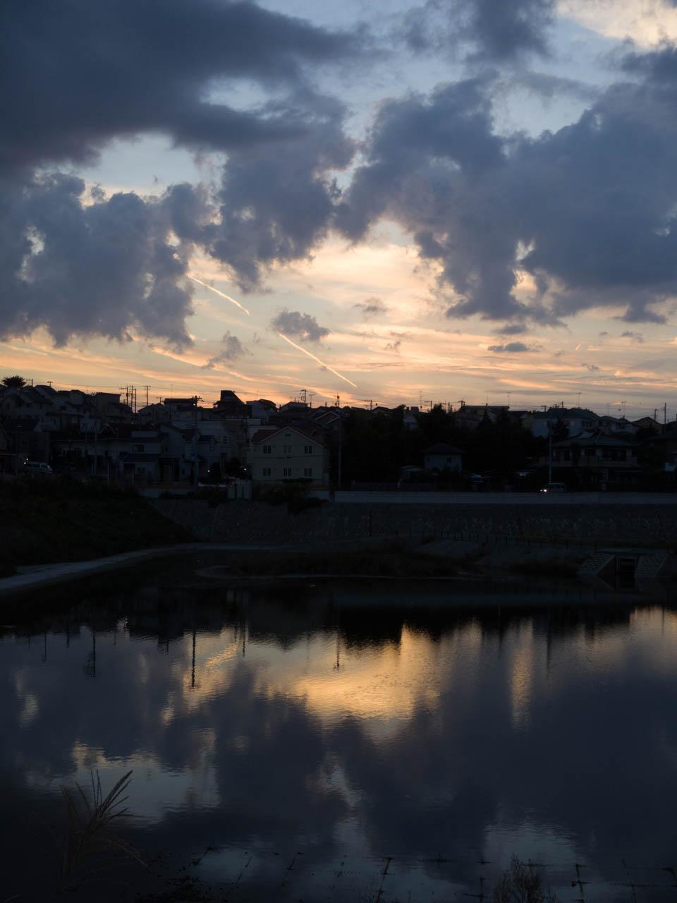 暮れてゆく街が、遊水地の湖面に写っていた